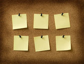 Six yellow notes pinned to grunge cork background — Stock Photo