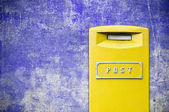 Yellow mail-box over grunge background — Stock Photo