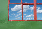 Blue coudy sky through old house window — Stock Photo