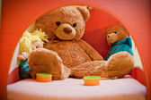 Children's toys lying in bed — Stock Photo