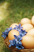 Flower decorated Easter eggs in brown natural basket — Stock Photo