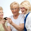 Elderly female friends with mobile device. - Stock Photo