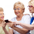 Three elderly women with cellphone. - Stock Photo