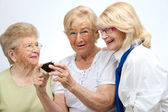 Elderly female friends with mobile device. — Stock Photo