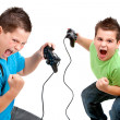 Euphorious boys playing with consoles - Stock Photo
