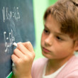 Close up of young student writing on chalkboard — Stock Photo