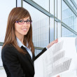 Portrait of young female architect with plans. — Stock Photo #9348171