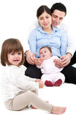 Unhappy jealous little girl with family — Stock Photo