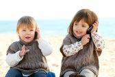 Two baby girls talking on mobile phones. — Stock Photo