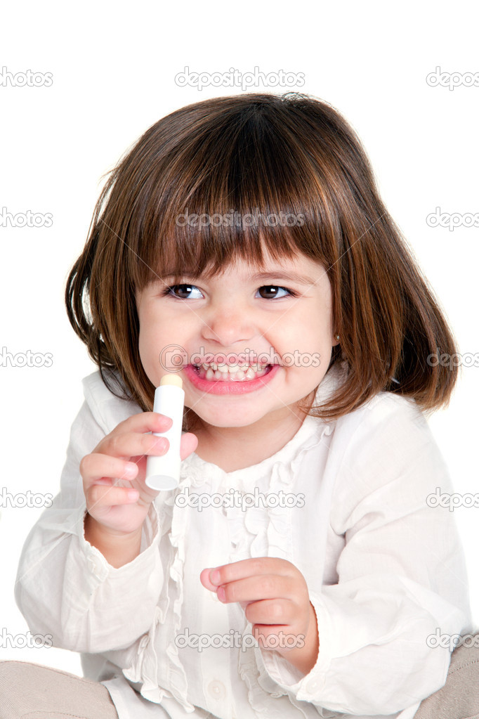 Portrait of cute little girl holding lip balm. Isolated on white background.  Stock Photo #9346768