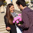 Boy surprising his girlfriend with flowers - Stok fotoğraf