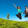 Happy couple jumping high — Stock Photo