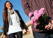 Boy surprising girlfriend with flowers — Stock Photo