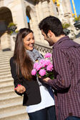 Boy surprising his girlfriend with flowers — Stock Photo