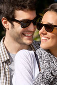 Close up portrait of smiling couple with sunglasses . — Stock Photo