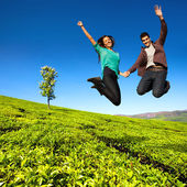 Jumping couple in green field. — Stock Photo