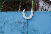 White horseshoe on a blue fence — Stock Photo