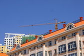 The roof of the house and construction crane — Stock Photo