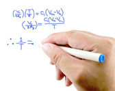 Teacher hand writing a mathematical equation on a white screen. — Foto de Stock