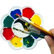 Artist palette with brushes on hand — Stok fotoğraf