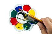 Paleta de artista con pinceles en mano — Foto de Stock