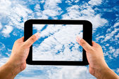 Tablet in hands on blue sky background — Stock Photo