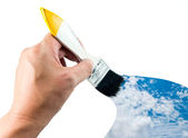 Hand holding brush and sky paint — Stock Photo