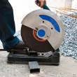 Worker using electric circular saw - Stock Photo