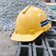 Yellow safety hard hat putting over bricks — Stock Photo