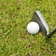 Iron golf club and golf ball on green grass — Stock Photo #10412848