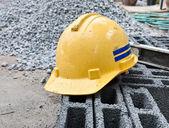 Yellow safety hard hat putting over bricks — Stock Photo
