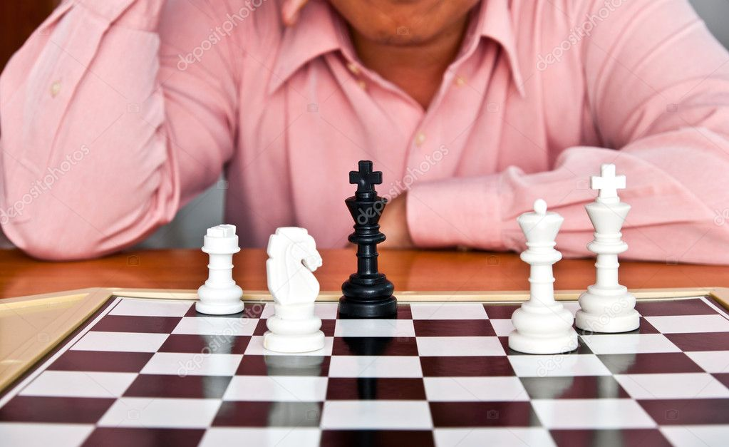 Man thinking about chess strategy   Stock Photo #10415975