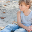 Little boy in deep thoughts playing in sandbox — Foto Stock