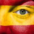 Flag painted on face with green eye to show Spain support — Stock Photo