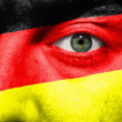 Flag painted on face with green eye to show Germany support — Stock Photo