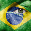 Flag painted on face with green eye to show Brazil support — Stock Photo