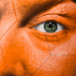 Football painted on orange face with green eye to show support — Stock Photo