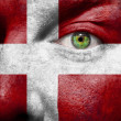 Flag painted on face with green eye to show Denmark support — Stock Photo