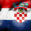 Flag painted on face with green eye to show croatia support — Stock Photo