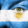 Flag painted on face with green eye to show argentina support — Stock Photo