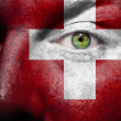 Flag painted on face with green eye to show Switzerland support — Stock Photo