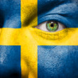 Flag painted on face with green eye to show sweden  support — Stock Photo