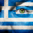 Flag painted on face with green eye to show greece support — Stock fotografie