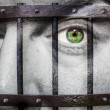 Face with green eye and painted prision — Stock Photo