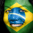 Smiling woman with brazil flag painted on her face — Stock Photo