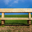 Bench situated on wood chips and grass against blue sky — Stock Photo