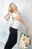 Happy young woman carrying shopping bags — Stock Photo