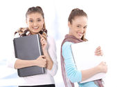 Portrait of smiling beautiful female students with notebooks — Stock Photo