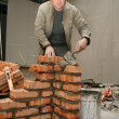 Mason in a hardhat building brick wall - Stock Photo