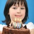 Happy girl with birthday cake on blue background (studio shot) — Stock Photo